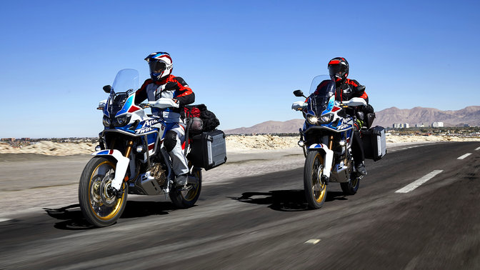 Deux pilotes conduisant les motos Honda Africa Twin Adventure Sports sur route.